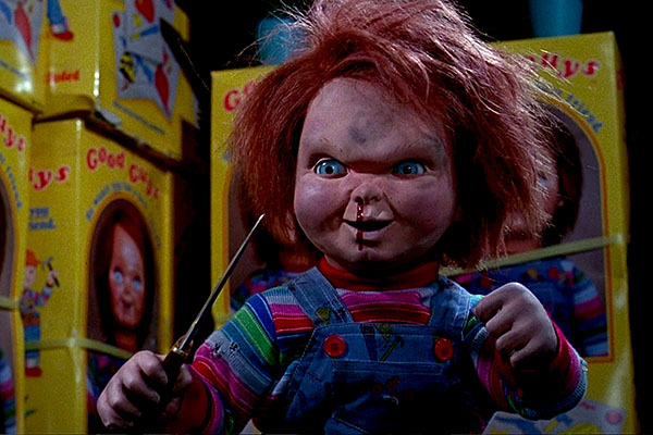 Chucky stands wielding a knife with blood gushing down his face from his dirty, toy nose.